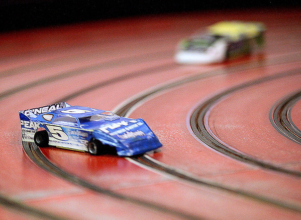 Brad Davis/The Register-Herald<br /> A pair of 1/24 scale modified stock cars whip around a turn on the Dirt Slotz race track Saturday night at it's 1010 Dry Hill Road location. This isn't slot car racing on that toy set you got for Christmas as a child. It's easy and inexpensive enough for both kids and adults, but does require some practice to get your timing and touch down. The slick characteristics of a dirt track make for drift-style racing like you'll see at Beckley Motor Speedway, meaning it can be easy to go too fast and spin your car, or even make contact with and spin other drivers when racing side-by-side. Here the #5 car, driven by 13-year-old Chase Evans, runs right on that fine line between a perfect turn and a spinout.