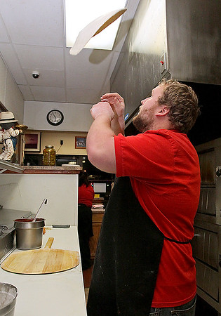 Brad Davis/The Register-Herald<br /> Padrino's employee Robbie Wotter lets the dough fly as he begins work on a hand-tossed pizza while working at the restaurant's Beckley Crossing location Sunday night.