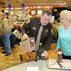 Rick Barbero/The Register-Herald<br /> Beckley City Police officer, Jake Corey, left, pours a cup of coffee for Betty Mills, of Beckley, at McDonald's on Robert C Byrd Drive near the Beckley Plaza Mall. Beckely City Police and McDonalds joined together Friday morning from 8:30 am to 10:30 am for a program called Coffe with a Cop.