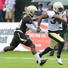 Rick Barbero/The Register-Herald<br /> Tim Hightower, right, runs away from Stanley Jean-Baptiste during the New Orleans Saints first day of practice held at The Greenbrier Resort in White Sulphur Springs Thursday morning.