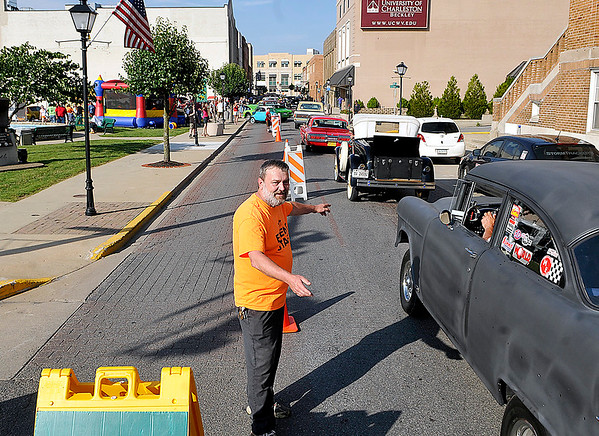 Brad Davis/The Register-Herald<br /> Volunteer Jeff Moorefield directs participants where to go as they cruise up Neville Street into uptown Beckley with restored classics and uniques customs during the opening moments of the Beckley Car & Bike Show Friday evening.