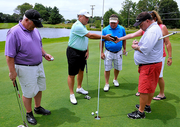 """Brad Davis/The Register-Herald<br /> Alan Wharton (right) applies a fresh layer of marker to the """"M"""" on his golf ball as Robert Wharton (2nd from left) gets a phone from his wife Mary Ann (hidden behind Alan) for pictures while Gary Wharton (2nd from right) and Randy Meadows prepare a quick memorial for their mother and Meadows' mother-in-law Barbara Wharton, who passed away just under a year ago. The three brothers played their entire rounds with the letter """"M"""" on their golf balls, while Meadows' ball carried a """"B"""" for Barabara."""