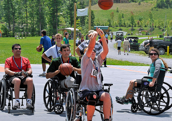 Brad Davis/The Register-Herald<br /> Boy Scout Jonathon Towner, of Troop 252 out of Toledo, Ohio, shoots from a wheelchair as Wounded Warrior Project veterans and others shoot hoops at the wheelchair basketball court during the Summit Bechtel Reserve's Veterans Appreciation Day Saturday afternoon in Fayette County. Most activities provided the opportunity for non-wheelchair bound veterans and anyone who wished to see what it's like living as a paralyzed veteran, while others chose to do it in solidarity. Photographed from left are Iraq War veterans Mark Lalli and Jonathan Pruden (holding ball), along with Mark's wife Margo (far right), who is able-bodied but was playing basketball in a chair.