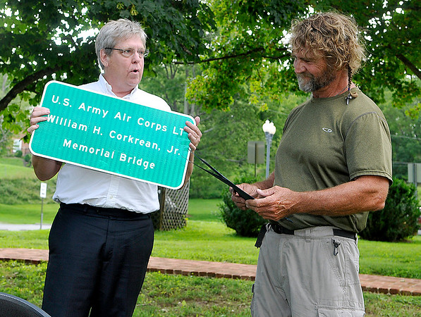 """Brad Davis/The Register-Herald<br /> State Senator Mike Woelfel (D-Cabell), left, presents a replica dedication road sign to Denver, Colorado resident Michael Marsh, nephew of World War II bomber pilot William """"Billy"""" Corkrean, Jr., who was shot down and killed during a mission over Belgium. Relatives and local officials gathered at Lewisburg's North House Museum Friday evening for the dedication of a bridge along Rt. 60 just outside the city which will now bear his name. The museum will also eventually receive some of Corkrean's personal items including his log book."""
