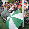 Brad Davis/The Register-Herald<br /> Fans in the front row of a sheltered grandstand get a little innovative with their umbrellas as they use them to make up legs area where the roof doesn't stop the rain along the 17th green during Greenbrier Classic action Friday in White Sulphur Springs.