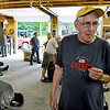 Brad Davis/The Register-Herald<br /> Korean War veteran Boyd Hiser talks about some of his experiences during the conflict as he snacks on a brownie Saturday while WVMV Veterans Support members work to assemble his World War II military jeep in Bill Miller's garage.