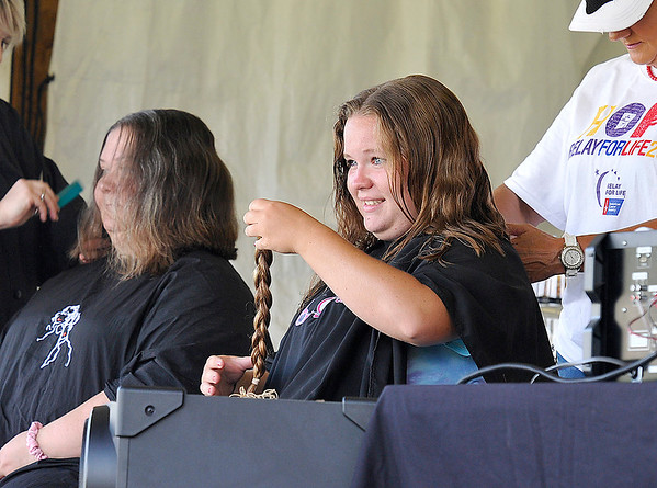 Brad Davis/The Register-Herald<br /> Shady Spring resident Jessie Kuhn, right, proudly shows off an 8-inch pony tail that she had chopped off as Beckley resident Corlettia Lilly, left, also gets her hair cut during Relay for Life events Friday evening at the YMCA Paul Cline Memorial Sports Complex. The two, along with several others in attendance, were donating at least eight inches of their hair for cancer patients who've lost theirs. It's the fourth time Kuhn has donated her hair, 14 inches of it this time around. Lilly, who's mother is a 46-year survivor, donates her hair every two years.
