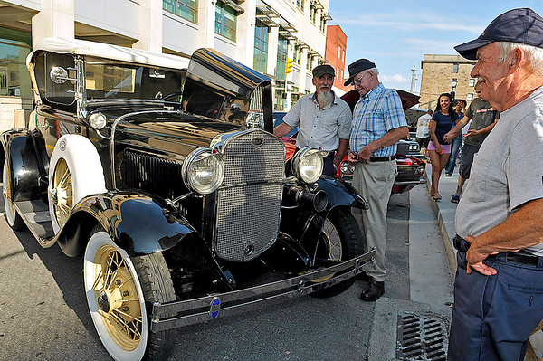 Brad Davis/The Register-Herald<br /> Classic car enthusiast and Whitesville resident Johnny Boggess (middle with beard) shows off his gorgeous 1931 Ford Model A Roadster to nearly awe-struck Beckley residents Stephen Bennett (nearest Boggess) and Russell Perkins (far right) during the Beckley Car & Bike Show Friday evening.