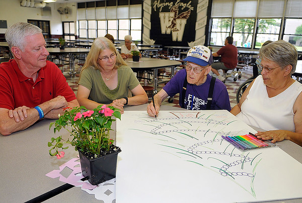 Brad Davis/The Register-Herald<br /> William Foley (2nd from right), a 13-year cancer survivor, signs his name to a special poster for cancer survivors and caregivers being passed around during the opening moments of the American Cancer Society's Relay for Life Survivor's Dinner Friday evening at Woodrow Wilson High School. Accompanying him and waiting for their turns are (from left) Wayne Davis, a seven-year survivor, caregiver Linda Treadway and fellow survivor Lois Bowling, Foley's daughter.