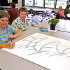 Brad Davis/The Register-Herald<br /> Cancer survivor Donna Ball, left, and caregiver Kay Forren take turns signing their names to a special poster for cancer survivors and caregivers being passed around during the opening moments of the American Cancer Society's Relay for Life Survivor's Dinner Friday evening at Woodrow Wilson High School.