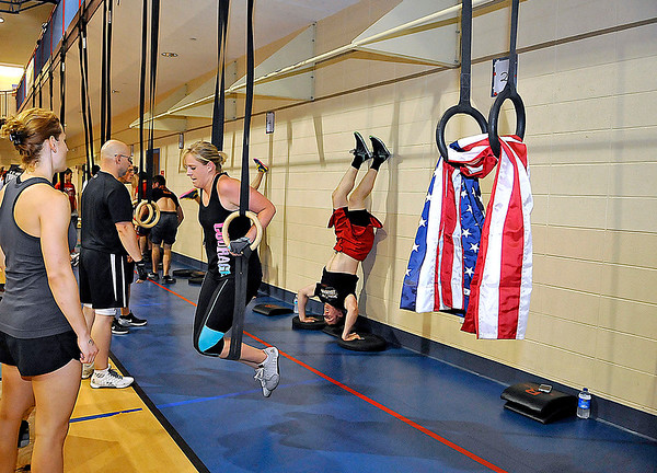 Brad Davis/The Register-Herald<br /> A lone pair of gym rings hang unoccupied with an American flag Saturday morning as crossfit enthusiasts workout in honor of 1994 Independence High Graduate and U.S. Navy SEAL Jeff Taylor, who was killed in action in Afghanistan on June 28, 2005. Friends, family and acquaintances gathered at The Place above United Methodist Temple to honor Taylor with a short ceremony on the 10th anniversary of his death, followed by a CrossFit-style workout as a tribute to his enthusiasm for physical fitness. Every single workout station was packed with workout teams except for one left open for Taylor, photographed at right.