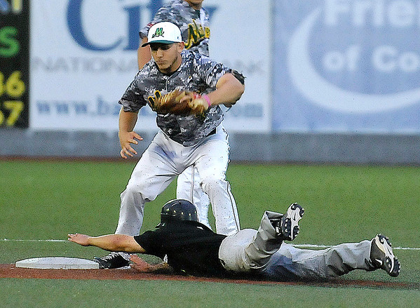 Brad Davis/The Register-Herald<br /> Miners second baseman Jonathan Weeks quickly pulls down a high throw in time to tag out Sliders player Brett Carbonneau on a steal attempt Thursday night at Linda K. Epling Stadium.