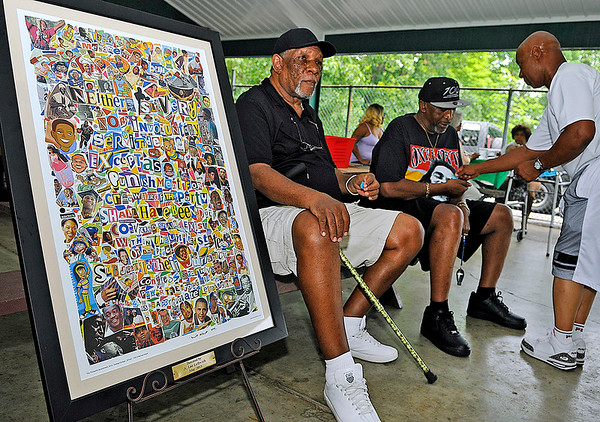 Brad Davis/The Register-Herald<br /> From left, Kenneth Phipps and Toney Mckeever sit beside a donated art work celebrating the 13th amendment as they get raffle tickets from organizer Tim Howard while hanging out and taking in festivities with fellow residents during a Community Cookout and Family Day Sunday afternoon at New River Park, the final event of a week that was full of Juneteenth Day festivities around Beckley. Juneteenth commemorates the general emacipation of African-Americans in 1863, but more specifically the announcement of President Lincoln's proclamation in Galveston, Texas, where in 1865 Union soldiers led my Maj. Gen. Gordon Granger landed there with news that the Civil War had ended and slavery had been abolished.