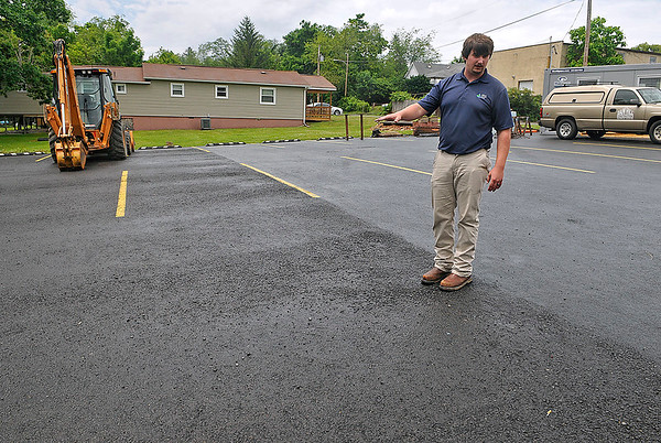 Brad Davis/The Register-Herald<br /> Nick Akers, an engineer with the Beckley Sanitary Board, describes the qualities of a new high-tech permeable parking lot at the Commission on Aging Wednesday afternoon. Situated on a grade, the upper portion of the lot (seen behind Akers) is surfaced just as any other lot would be, while the lower portion, seen at left, is permeable to allow runoff to seep back into the ground before it can run off into streams below.