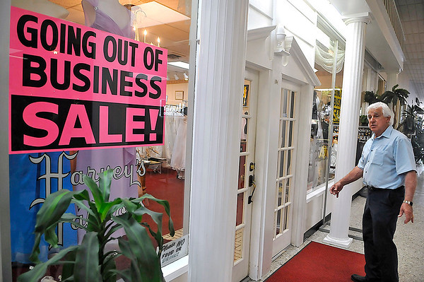 """Brad Davis/The Register-Herald<br /> Harvey's Bridal & Fashions co-owner Tom Harvey walks back into the store, currently riddled with closeout sale signage, as he chats with The Register-Herald Wednesday afternoon. After 40 years, the Harveys are closing the shop in a few months, though not for a lack of business. The brothers and their families simply want to """"slow down,"""" saying that getting back down to a 40 hour work week would feel like part-time."""