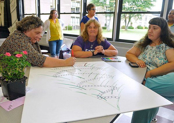 Brad Davis/The Register-Herald<br /> Sarah Massey, left, Martha Richmond, middle, and Brandy Redden take turns signing their names to a special poster for cancer survivors and caregivers being passed around during the opening moments of the American Cancer Society's Relay for Life Survivor's Dinner Friday evening at Woodrow Wilson High School. Massey was signing as a caregiver while Richmond and Redden signed as cancer survivors.