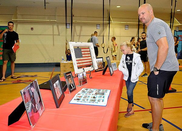 Brad Davis/The Register-Herald<br /> Area residents Keith Webb and his daughter Caroline, 7, look over photographs of late U.S. Navy SEAL Jeff Taylor and other memorabilia during a memorial ceremony Saturday morning at The Place above United Methodist Temple.