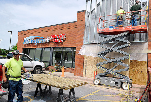 Brad Davis/The Register-Herald<br /> Agsten Construction workers (from left) David White, Sean Davis and Chad Heaster upgrade the front of the building currently housing MedExpress Thursday afternoon at their Beckley Crossing location.