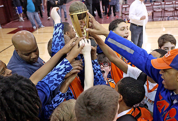 Brad Davis/The Register-Herald<br /> Charleston Cavaliers players reach up to get their hands on the championship trophy after defeating WV Burn in the 6th grade Biddy Buddy Tournament final Sunday afternoon at Woodrow Wilson High School.