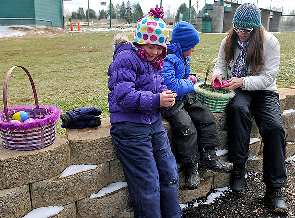 Brad Davis/The Register-Herald<br /> Six-year-old Ava Emery, left, wastes no time along with her little brother Sawyer, 4, and mother Lisa in cracking open her bounty of easter eggs Saturday afternoon at Fayetteville's Town Park.