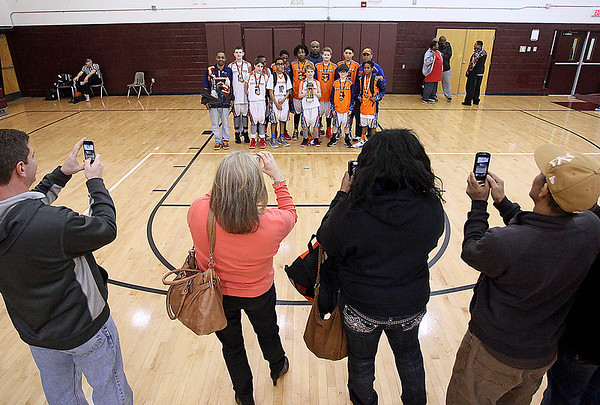 Brad Davis/The Register-Herald<br /> Parents and relatives make sure they get their shot as the Charleston Cavaliers pose with the championship trophy after defeating WV Burn for the 6th grade Biddy Buddy title Sunday afternoon at Woodrow Wilson High School.