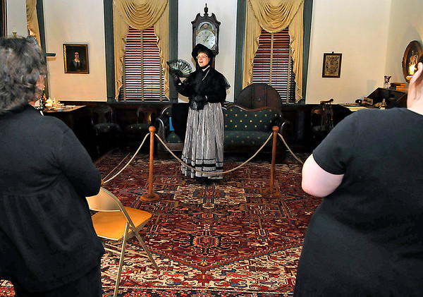 """Brad Davis/The Register-Herald<br /> Visitors watch as """"Minnie Anderson,"""" played by Elizabeth Spangler, tells the story of her life from the time she was a belle at the Old White to the time she left Lewisburg for good around 1870 to move to New York, being married and widowed three separate times in the process. The monologue was an example of the mourning rituals of society during the victorian era, the focus of North House Museum's latest exhibit, """"Mourning in America."""" The story of Minnie Anderson herself isn't one of fiction. She was a real-life woman who lived around the White Sulpher Springs and Lewisburg areas during the early to mid 1800's."""