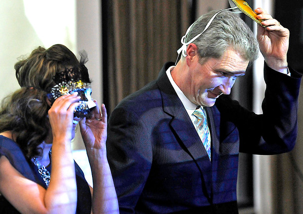 Brad Davis/The Register-Herald<br /> Couple number five, better known as Oak Hill's Alicia Dempsey Morabito and her partner Dr. Bill Klenk, remove their mass as they're introduced during the United Way of Southern West Virginia's Swing into Spring event, where six couples were announced as contestants in this year's upcoming Dancing With The Stars Thursday night at Black Knight Country Club.