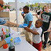 Brad Davis/The Register-Herald<br /> Beckley resident Tobias Gibbons, 4, gets his snow cone from Jan-Care Ambulance's John Parker while his older brother Tayshawn, 11, is already sipping his during Beckley's Sweet Treats event Saturday afternoon at the Intermodal Gateway.