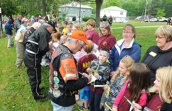 Rick Barbero/The Register-Herald<br /> Bikers sign autographs in front of Rainelle Elementary school after they paraded through the town of Rainelle Thursday afternoon.