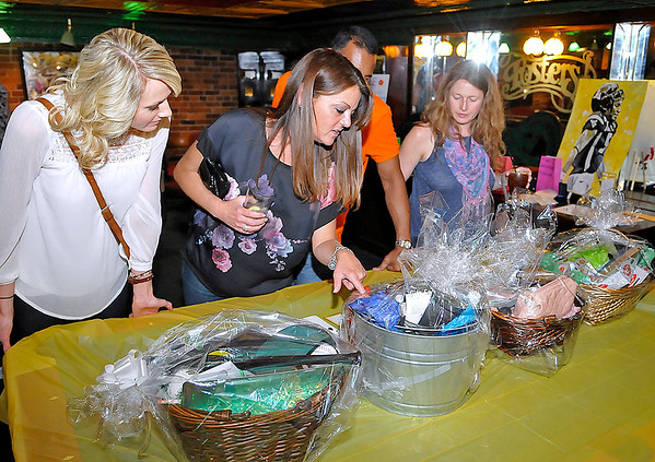 Brad Davis/The Register-Herald<br /> Patrons (from left) Ashley Ratliff, Sarah Smith, Bryant Kittle (behind Smith) and Carolyn Buzbee browse silent auction items during a benefit event for 13-year-old Hannah Snuffer Friday night at Foster's Main Street Tavern.