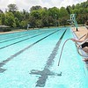 Rick Barbero/The Register-Herald<br /> Kristin Duguid, lifeguard at New River Park pool, drops a water hose down into the pool preparing the pool for the summer season.