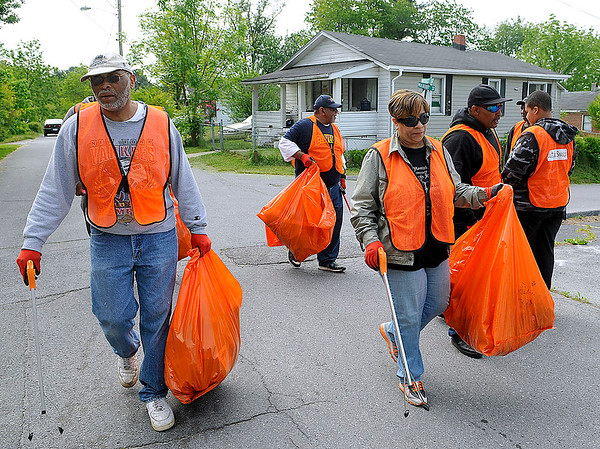 Brad Davis/The Register-Herald<br /> Volunteers make their way along Brooks Street carrying bags full of garbage picked up along the streets of East Beckley Saturday morning. From left are Joe Johnson, Richard Dobson, Debra Cross, David Green and his his son David Jr. They, along with several other volunteers from Heart of God Ministries at 1703 South Kanawha Street, were out from about 7:00 a.m. until noon removing weeds and garbage in the areas from Koch Avenue to F Street through Barber and Antonio Avenues.