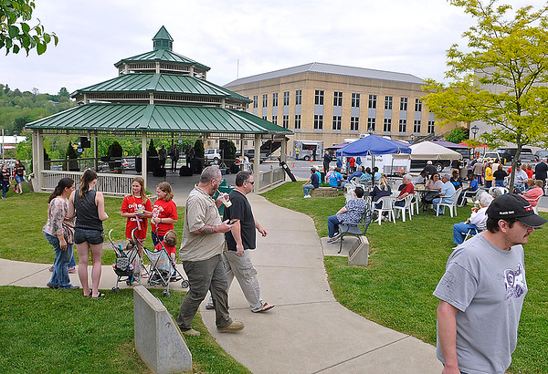 Brad Davis/The Register-Herald<br /> Area residents mingle and relax on a nice afternoon at Word Park in uptown Beckley as the gospel group Heaven's Harmony performs under the gazebo during the season's first Friday in the Park yesterday. The 25th season of the local event kicked off with Coal City Elementary's choir prior to Heaven's Harmony's performance, with Patricia Smith from Abundance of Blessings Music slated to perform next week.