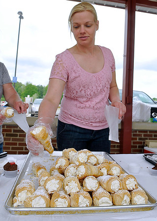 Brad Davis/The Register-Herald<br /> The Bake Shoppe co-owner Christen Blackburn bags up fresh pastries for patrons during Beckley's Sweet Treats event Saturday afternoon at the Intermodal Gateway.