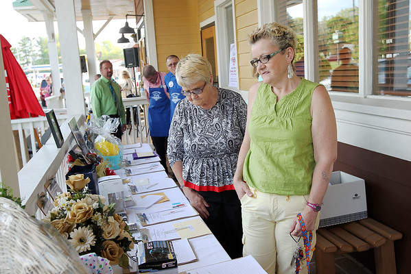 Chris Jackson/The Register-Herald<br /> Sheila Shelton, right, and Gladys Lester, both of Herndon, look over the auction setup at Outback Steakhouse on Harper Rd. in Beckley during Celebrity Night on Monday, May 4, 2015.