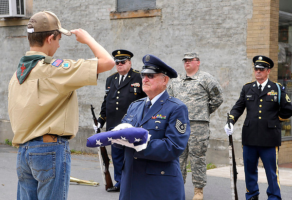 Brad Davis/The Register-Herald<br /> Scout Zach Milam (left) from Troop 75 out of Sophia presents a folded American flag to American Legion Post 149 (Fayetteville) Military Honor Guard member Vernon Barley during a re-dedication ceremony for the town's World War I monument Saturday afternoon.