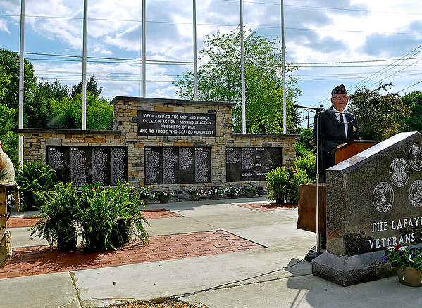 Brad Davis/The Register-Herald<br /> Moderator Paul Blake (at podium) of the Fayetteville American Legion Post 149 speaks moments after the cover is pulled off unveiling the brand new Lafayette Huse Veterans Memorial during a ceremony at the city's town park Saturday afternoon.