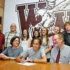 Brad Davis/The Register-Herald<br /> Woodrow Wilson athlete Emily Fedders (middle with pen) signs a letter of intent to join the track and field program at Appalachian State University surrounded by her parents Barbara (left of Emily) and Jim, along with friends, family and coaches Wednesday afternoon at Woodrow Wilson High School.