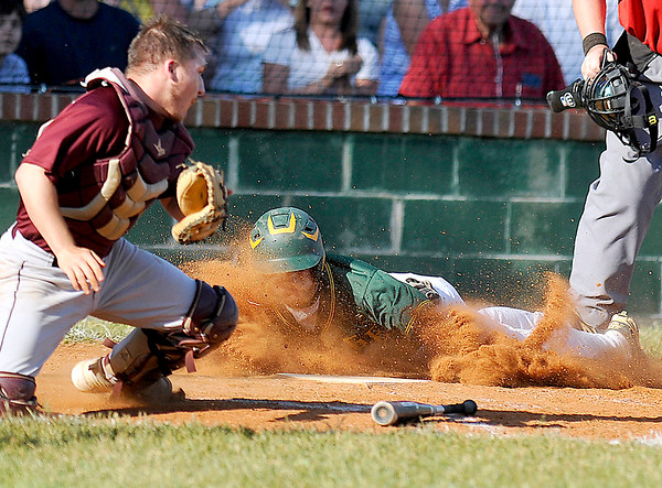 Brad Davis/The Register-Herald<br /> The ball skips away from Woodrow Wilson catcher Dylan Foster as Greenbrier East's Colby Johnson sends up a wall of dirt diving head first into home to score a run during the Spartans' win over the Flying Eagles Monday evening in Fairlea.