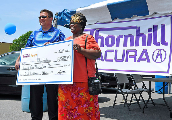 Brad Davis/The Register-Herald<br /> Beckley resident Robin Harbison poses for a quick photo with Thornhill Automotive General Manager Lee Neal as he presents her with a $25,000 check, the grand prize in a recent scratch-and-win game, Saturday afternoon at Crossroads Mall.