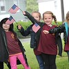 Rick Barbero/The Register-Herald<br /> Katelyn Rogers, left, Ella Berry, Aurora Gunnoe and Paydaence Gus, students at Rainelle Elementary School, wave flags to over 500 bikers that paraded through the town of Rainelle Thursday afternoon as they make their Run for the Wall to Washington, DC