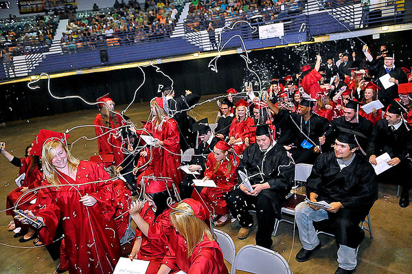 Brad Davis/The Register-Herald<br /> Newly graduated Liberty High seniors, some taking cover and some joining in the fray, erupt in celebration at the conclusion of their commencement ceremony Saturday afternoon at the Beckley-Raleigh County Convention Center.