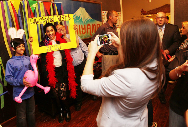 Chris Jackson/The Register-Herald<br /> Morgan Walls, right, with United Bank, snaps a photo of some guests at Fujiyama's Celebrity Night in Beckley on Monday, May 4, 2015.