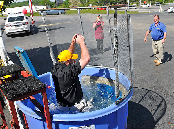Brad Davis/The Register-Herald<br /> Mountaineer Automotive service manager Roger Cogar plunges into the chilly pool of water as his employee, service advisor Jimmy Parrish (upper far right), enjoys the sight after hitting the target during a Red Nose Day fundraising event Wednesday afternoon. Mountaineer offered to let people dunk their employees during the bake sale and radio event, all to raise money to help children and young people living in poverty. Mountaineer matched all the funds raised, which was nearing $1,000 by event's end.