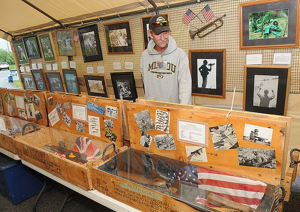Rick Barbero/The Register-Herald<br /> Glen Blake, of Ofallon, MO, looks over the Through the Eyes display during the Veteran's Reunion held in Rainelle. The display contains over 2,000 pieces of Vietnam era memorabilia and combat photographs.