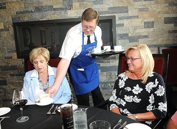 Rick Barbero/The Register-Herald<br /> Ed Wills, Beckley Fire Chief, center, serves Dina Jones, of Crab Orchard, left, and Pam Dohm, of Charleston, during Celebrity Night Monday at Black Knight Country Club