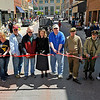 Brad Davis/The Register-Herald<br /> A mixture of veterans and area residents cut the ceremonial ribbon as the Neville Street Market opens up Saturday morning in uptown Beckley. From left are veterans Jim Chambers (Navy 1969-76), Eva Pettry (Marine Corps. 1965-69), Russ Weeks (4th from left, Navy 1959-78), James Ash (4th from right, Army 1969-71) and Raleigh County Veterans Museum director James Toler (2nd from right).