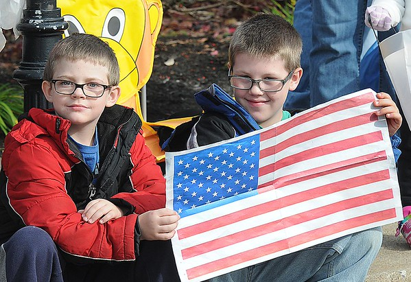 Rick Barbero/The Register-Herald<br /> Joel Plummer, 8, left, and his twin brother, Like Plummer, 8, sons of Michael and Sharon Plummer, of Beckley, hold up a paper American flag during the Beckley Veterans Day Parade held in downtown Beckley late Friday morning.