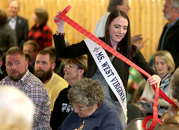 Brad Davis/The Register-Herald<br /> A patron at far left seems to react as he notices the massive amount of 50/50 tickets being unravelled for another by Ms. West Virginia Jennifer Skaggs during the United Way's annual Wonderland of Trees charity auction event Friday night inside the Crossroads Mall.