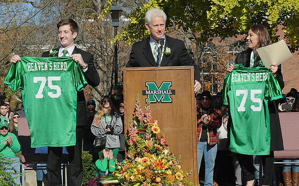 Rick Barbero/The Register-Herald<br /> Stephen Ward. keynote speaker, center, presented Duncan Waugaman, student body presiodent, left, and Isabelle Rogner, student body vice president, with Marshall jersey's during Marshall University annual fountain ceremony at the Memorial Student Center Plaza Saturday morning honoring the 45th anniversary of the crash of Southern Airways Flight 932—a chartered airliner carrying the 1970 Marshall Football team that killed all 75 passengers and crew on board. The fountain, made of 75 upward-pointing rods to represent the victims, is turned off every year at the ceremony and remains off until spring practice begins for the following season. In all, 37 players, eight coaches, 25 fans and five crew members were killed in what stands as one of the worst tragedies in collegiate sports history.